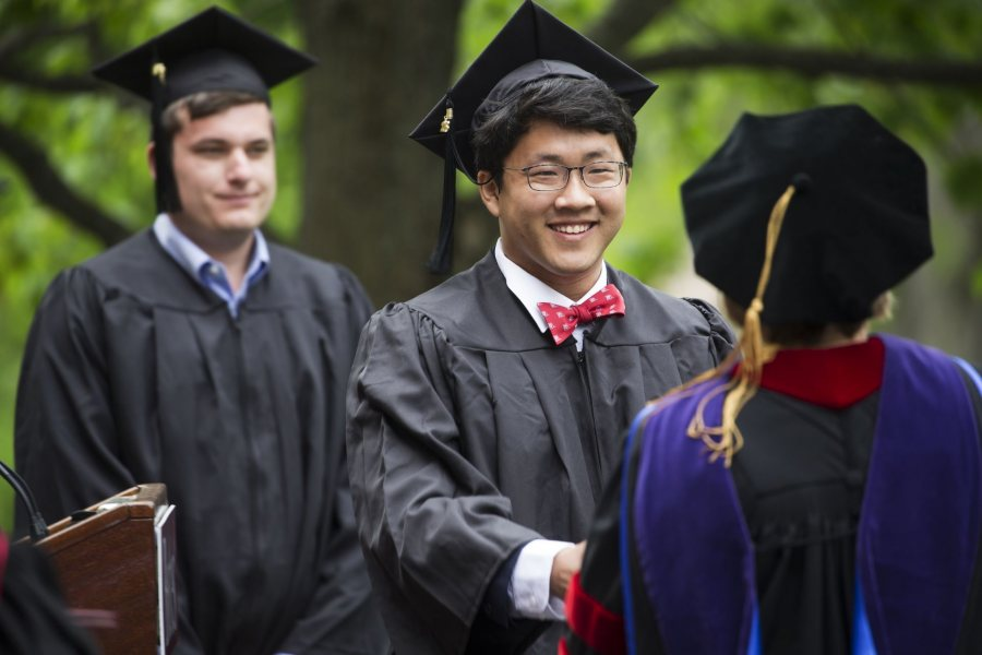 Elliot Chun, of Bedford N.H., receives his diploma while celebrating Bates 152nd Commencement on May 27, 2018.