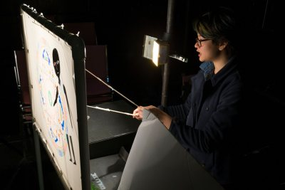 "Keila Ching '18 of Honolulu, Hawaii, a student in ""Epics of Asia"" taught by Assistant Professor of Religious Studies Alison Melnick, performs her final project in the Black Box Theater. For their finals, the students were asked to reinterpret an epic myth in a format of their choice, and Ching opted to create a shadow puppet performance featuring a prologue to the Tibetan myth of Gesar of Ling"