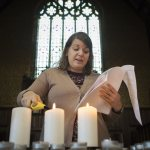 "Multifaith Chaplain Brittany Longsdorf lights a candle while speaking during a 9/11 Moment of Remembrance at the Chapel Monday morning. ""We light a candle in remembrance for all those who suffered and died on September 11th in New York, Pennsylvania and at the Pentagon in Arlington, Virginia.  We light a candle to remember those who still live and who suffer because of the events of that day,"" said Longsdorf."