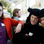 "Dressed as ""Behometh, the devil's anthropomorphic cat,"" Professor of Russian Dennis Browne (center) joins Emma White '11 of Bainbridge Island, Wash., as ""Koroviev"" (left) and Elizabeth Rie '09 of White Plains, N.Y., as ""Azazello"" (right) for the students' poster on the autobiographical aspects of Mikhail Bulgakov's novel ""The Master and Margarita."""